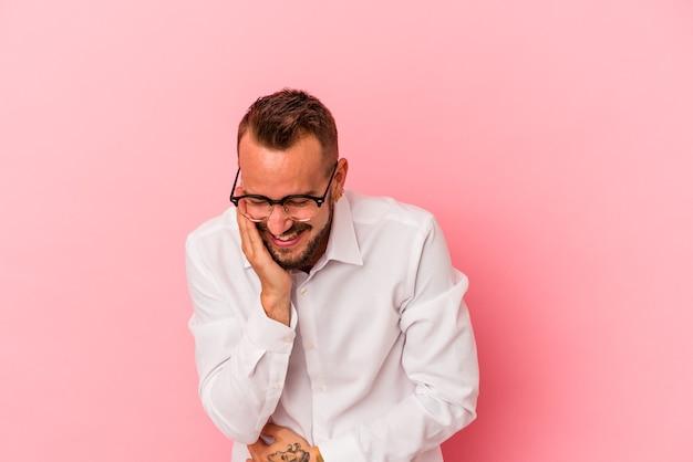 Jeune homme de race blanche avec des tatouages isolés sur fond rose rit joyeusement et s'amuse à garder les mains sur le ventre.