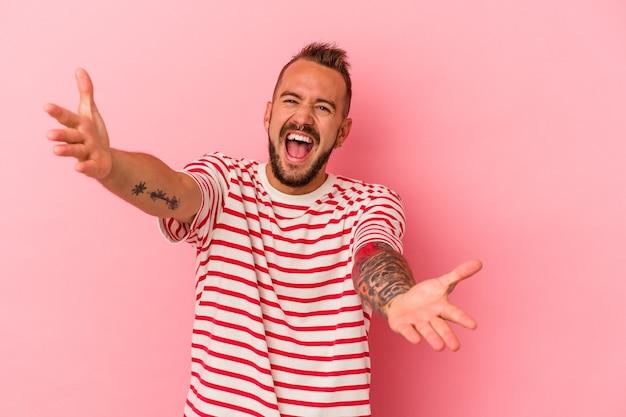 Jeune homme de race blanche avec des tatouages isolés sur fond rose se sent confiant en donnant un câlin à la caméra.