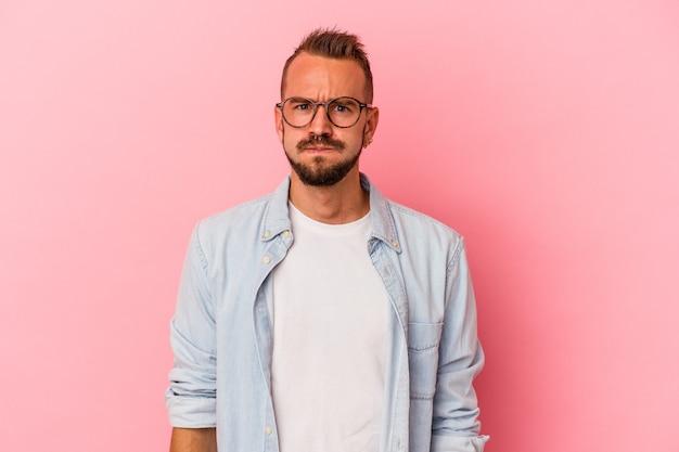 Jeune homme de race blanche avec des tatouages isolés sur fond rose souffle les joues, a une expression fatiguée. concept d'expression faciale.