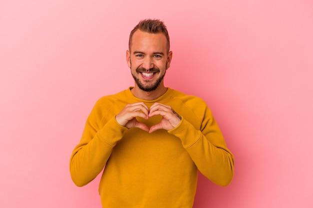 Jeune homme de race blanche avec des tatouages isolés sur fond rose souriant et montrant une forme de coeur avec les mains.