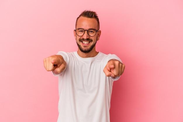 Jeune homme de race blanche avec des tatouages isolés sur fond rose sourires joyeux pointant vers l'avant.