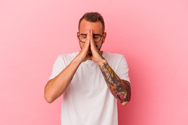 Jeune homme de race blanche avec des tatouages isolés sur fond rose tenant les mains en prière près de la bouche, se sent confiant.