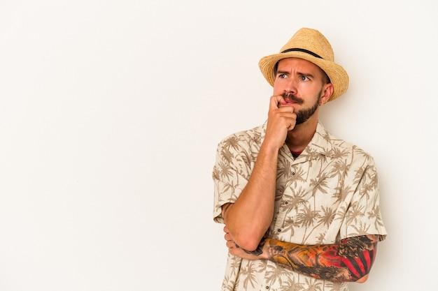 Jeune homme de race blanche avec des tatouages portant des vêtements d'été isolés sur fond blanc détendu en pensant à quelque chose en regardant un espace de copie.