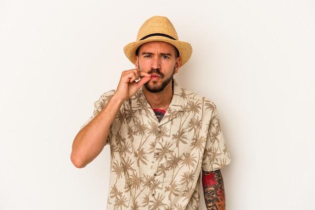Jeune homme de race blanche avec des tatouages portant des vêtements d'été isolés sur fond blanc avec les doigts sur les lèvres gardant un secret.