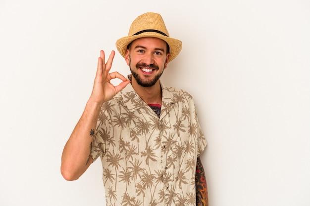 Jeune homme de race blanche avec des tatouages portant des vêtements d'été isolés sur fond blanc joyeux et confiant montrant un geste correct.