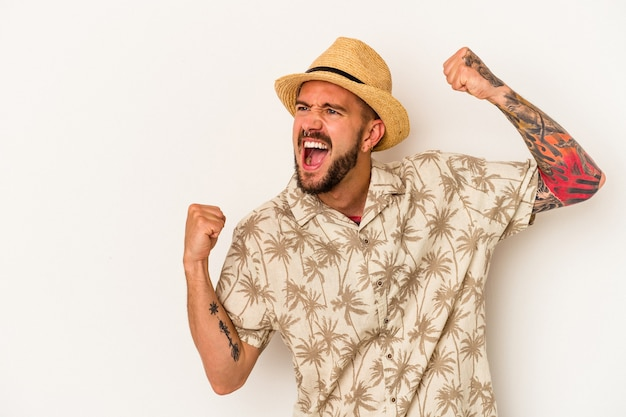 Jeune homme de race blanche avec des tatouages portant des vêtements d'été isolés sur fond blanc levant le poing après une victoire, concept gagnant.