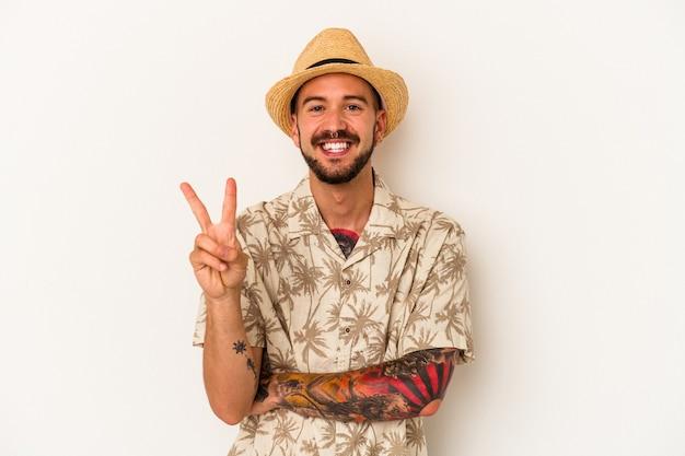 Jeune homme de race blanche avec des tatouages portant des vêtements d'été isolés sur fond blanc montrant le numéro deux avec les doigts.
