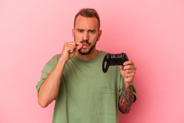 Jeune homme de race blanche avec des tatouages tenant un contrôleur de jeu isolé sur fond rose avec des doigts sur les lèvres gardant un secret.