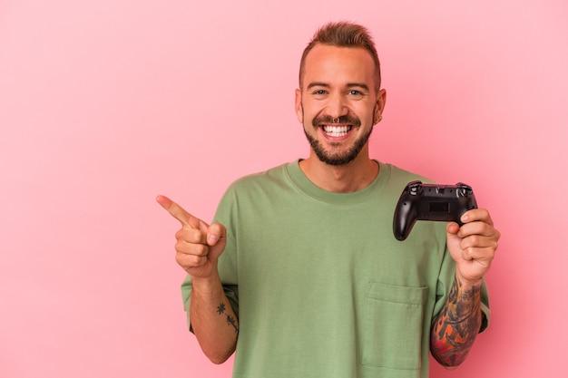 Jeune homme de race blanche avec des tatouages tenant un contrôleur de jeu isolé sur fond rose souriant et pointant de côté, montrant quelque chose dans un espace vide.