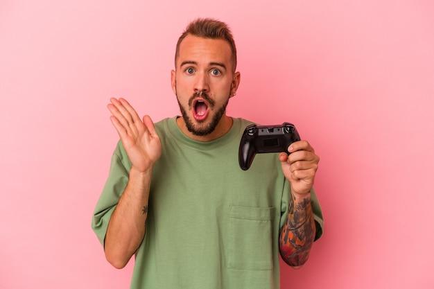Jeune homme de race blanche avec des tatouages tenant un contrôleur de jeu isolé sur fond rose surpris et choqué.
