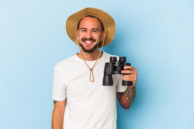 Jeune homme de race blanche avec des tatouages tenant des jumelles isolées sur fond bleu heureux, souriant et joyeux.