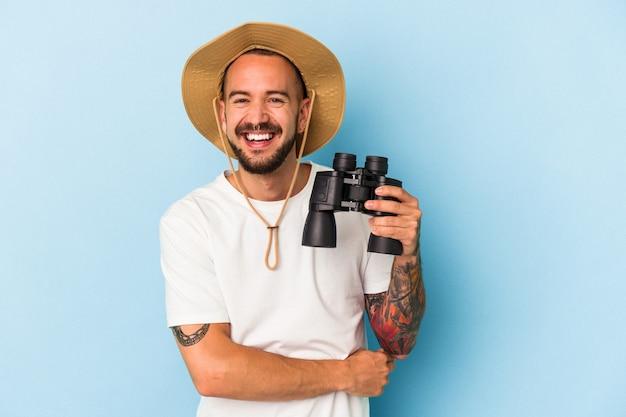 Jeune homme de race blanche avec des tatouages tenant des jumelles isolées sur fond bleu en riant et en s'amusant.