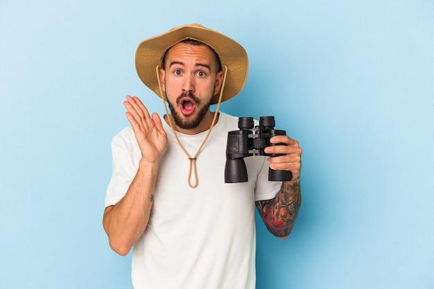 Jeune homme de race blanche avec des tatouages tenant des jumelles isolées sur fond bleu surpris et choqué.