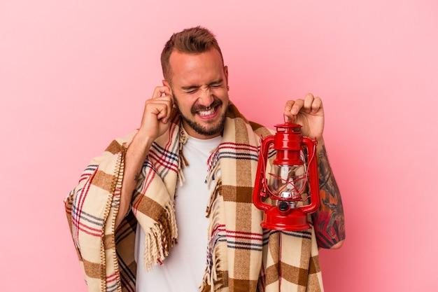 Jeune homme de race blanche avec des tatouages tenant une lanterne vintage isolée sur fond rose couvrant les oreilles avec les mains.