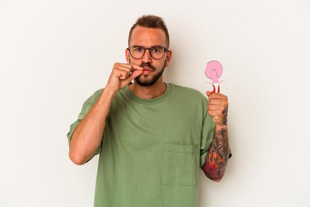 Jeune homme de race blanche avec des tatouages tenant une sucette isolée sur fond blanc avec les doigts sur les lèvres gardant un secret.