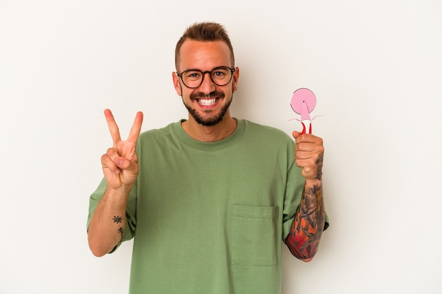 Jeune homme de race blanche avec des tatouages tenant une sucette isolée sur fond blanc montrant le numéro deux avec les doigts.