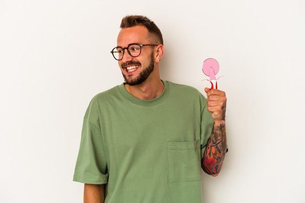 Jeune homme de race blanche avec des tatouages tenant une sucette isolée sur fond blanc regarde de côté souriant, joyeux et agréable.