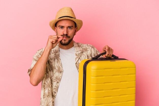 Jeune homme de race blanche avec des tatouages va voyager isolé sur fond rose avec les doigts sur les lèvres gardant un secret.