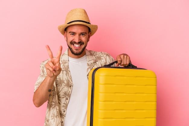 Jeune homme de race blanche avec des tatouages va voyager isolé sur fond rose montrant le numéro deux avec les doigts.