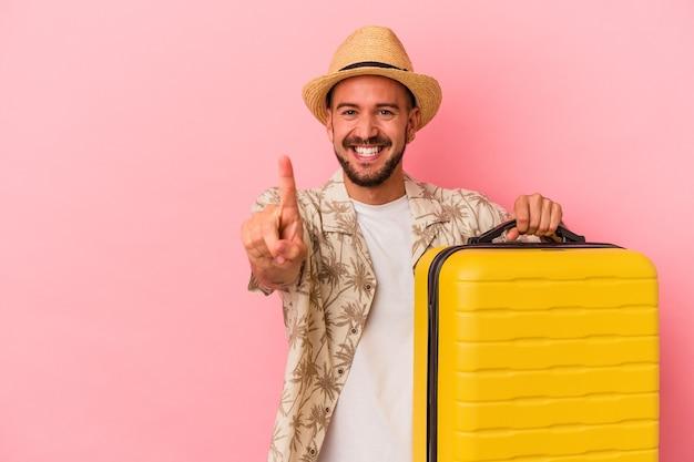 Jeune homme de race blanche avec des tatouages va voyager isolé sur fond rose montrant le numéro un avec le doigt.