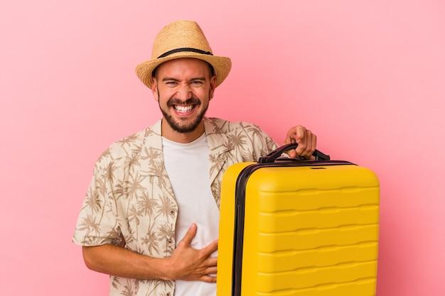 Jeune homme de race blanche avec des tatouages va voyager isolé sur fond rose en riant et en s'amusant.