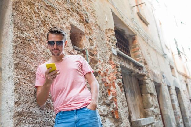 Jeune homme de race blanche avec téléphone portable dans la ville européenne