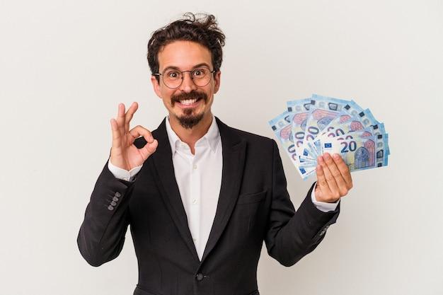 Jeune homme de race blanche tenant des billets isolés sur fond blanc joyeux et confiant montrant un geste ok.