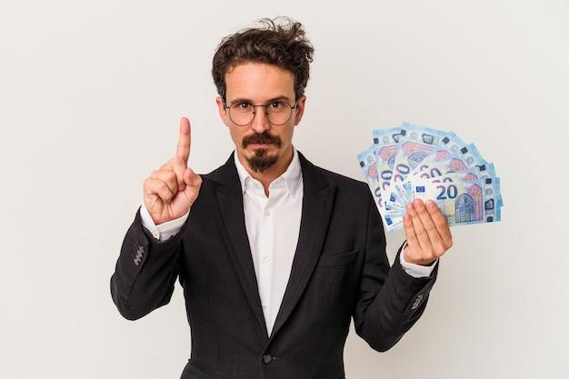 Jeune homme de race blanche tenant des billets isolés sur fond blanc montrant le numéro un avec le doigt.