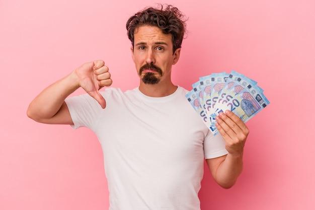 Jeune homme de race blanche tenant des billets isolés sur fond rose montrant un geste d'aversion, les pouces vers le bas. notion de désaccord.