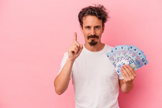 Jeune homme de race blanche tenant des billets isolés sur fond rose montrant le numéro un avec le doigt.