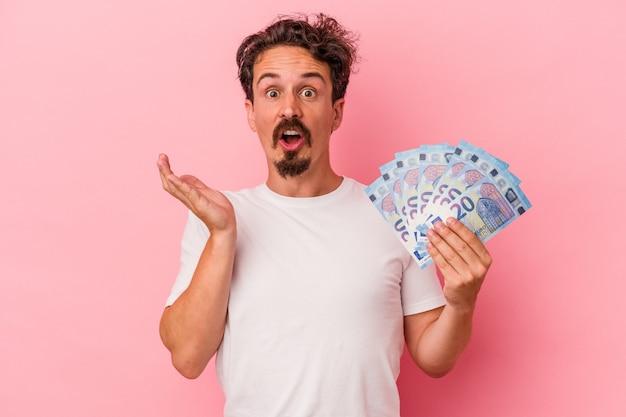 Jeune homme de race blanche tenant des billets isolés sur fond rose surpris et choqué.