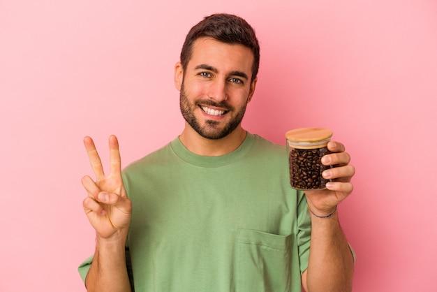Jeune homme de race blanche tenant une bouteille de café isolée sur un mur rose montrant le numéro deux avec les doigts