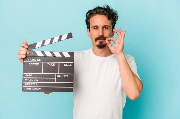 Jeune homme de race blanche tenant un clap isolé sur fond bleu avec les doigts sur les lèvres gardant un secret.
