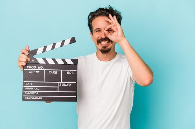 Jeune homme de race blanche tenant un clap isolé sur fond bleu excité en gardant le geste ok sur les yeux.