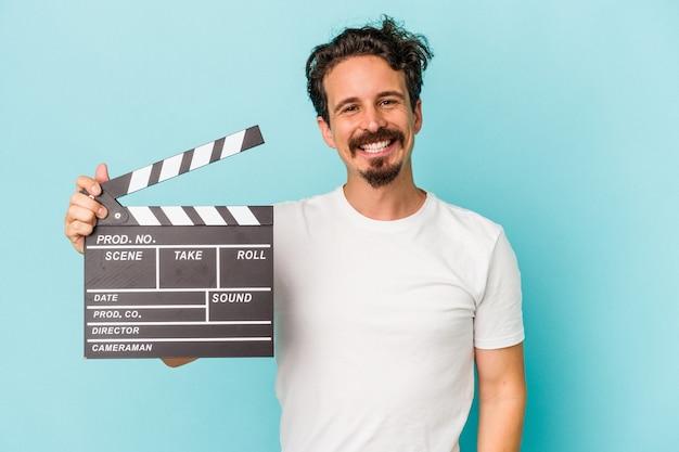 Jeune homme de race blanche tenant un clap isolé sur fond bleu heureux, souriant et joyeux.