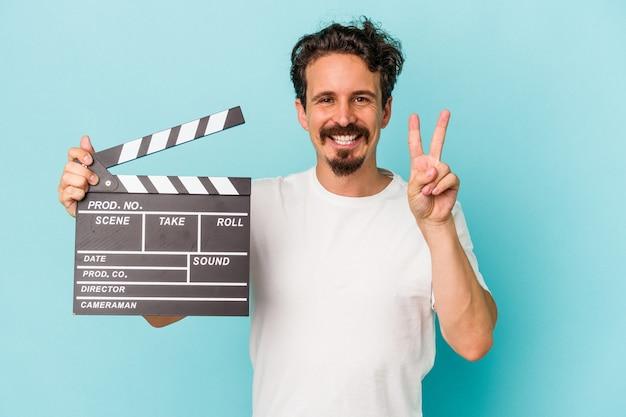 Jeune homme de race blanche tenant un clap isolé sur fond bleu montrant le numéro deux avec les doigts.