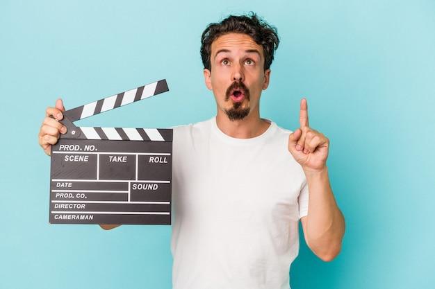 Jeune homme de race blanche tenant un clap isolé sur fond bleu pointant vers le haut avec la bouche ouverte.
