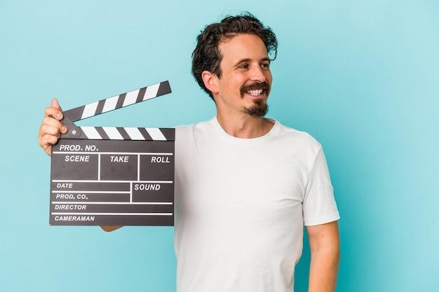 Jeune homme de race blanche tenant un clap isolé sur fond bleu regarde de côté souriant, joyeux et agréable.