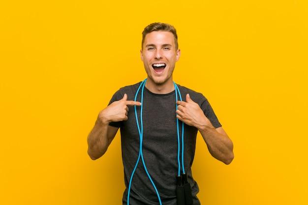 Jeune homme de race blanche tenant une corde à sauter surpris, pointant le doigt vers lui-même, souriant largement.