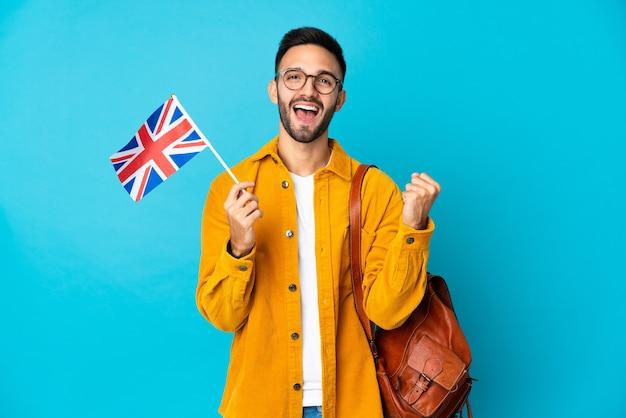 Jeune homme de race blanche tenant un drapeau du royaume-uni isolé sur fond jaune célébrant une victoire en position de vainqueur