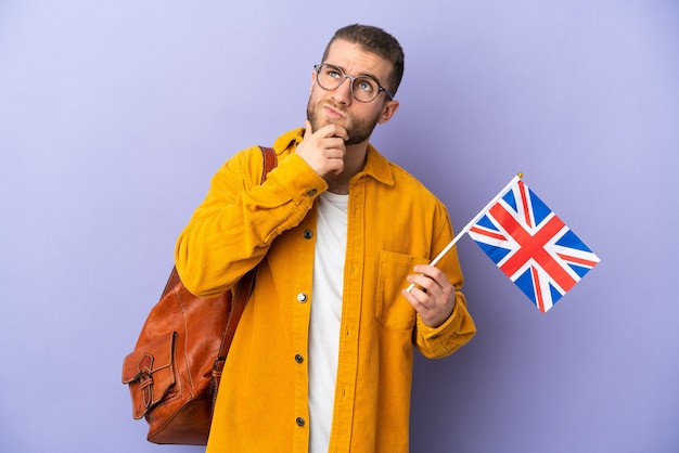Jeune homme de race blanche tenant un drapeau du royaume-uni isolé sur violet ayant des doutes