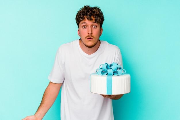 Jeune homme de race blanche tenant un gâteau isolé sur fond bleu hausse les épaules et ouvre les yeux confus.