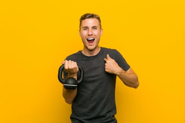 Jeune homme de race blanche tenant un haltère surpris pointant sur lui-même, souriant largement.