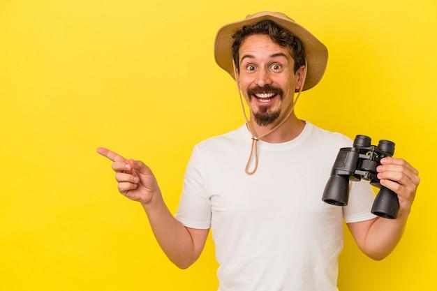 Jeune homme de race blanche tenant des jumelles isolées sur fond jaune souriant et pointant de côté, montrant quelque chose dans un espace vide.