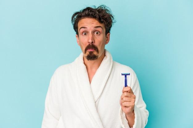 Jeune homme de race blanche tenant une lame de rasoir isolée sur fond bleu hausse les épaules et ouvre les yeux confus.