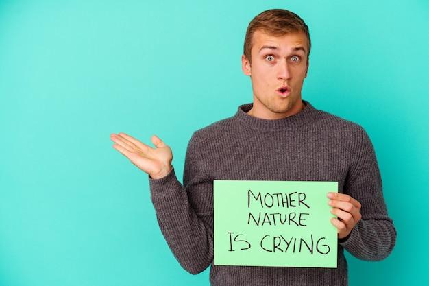 Jeune homme de race blanche tenant une mère nature pleure une pancarte isolée sur bleu impressionné tenant un espace de copie sur la paume.