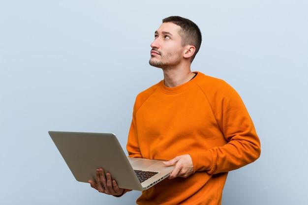 Jeune homme de race blanche tenant un ordinateur portable souriant confiant avec les bras croisés.