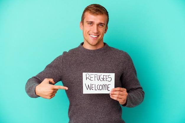 Jeune homme de race blanche tenant une pancarte de bienvenue de réfugiés isolé sur mur bleu