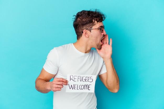Jeune homme de race blanche tenant une pancarte de bienvenue de réfugiés isolés criant et tenant la paume près de la bouche ouverte