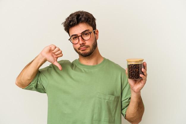 Jeune homme de race blanche tenant un pot de café isolé sur fond blanc montrant un geste d'aversion, les pouces vers le bas. notion de désaccord.